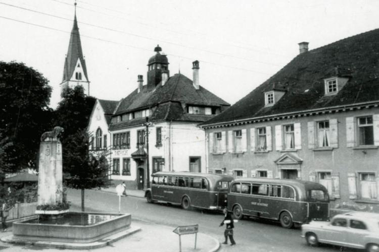 In den 1950er Jahren waren Bus-Züge in Konstanz unterwegs. Das Bild zeigt einen Bus mit Anhänger vor dem Rathaus in Wollmatingen. (Quelle: Stadtarchiv Konstanz)