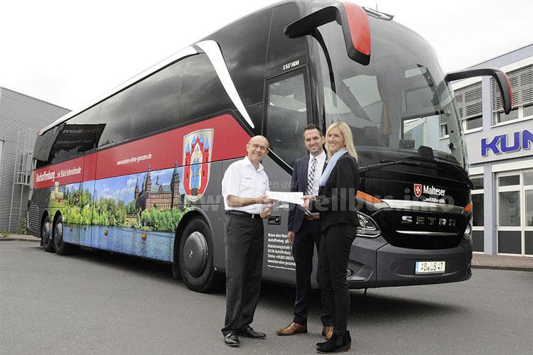 Busunternehmer Werne Henke (links) bekommt von den Aftersales-Mitarbeitern Martina Schmitt und Hans-Jürgen Bühler den 1000 Omniplus Service-Vertrag Premium überreicht.